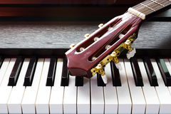 Guitar neck on piano keys. Guitar neck on piano keyboard royalty free stock images