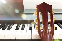 Guitar neck and piano. Stock Photography