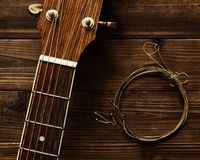 Guitar Neck And Strings. Acoustic guitar neck and old strings on wood in natural light stock photo