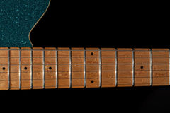 Guitar neck at the 12th fret. Maple fretboard portion on blue gl. Itter electric rock guitar. Instrument neck shown against plain black background with copy Royalty Free Stock Photography