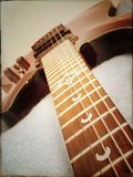 Guitar neck towards body. Fretboard and strings Stock Photography