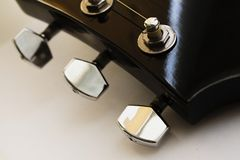 Guitar neck with tuning pegs. On a light background Royalty Free Stock Image