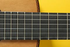Guitar neck on yellow background. Closeup royalty free stock photos