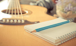 Guitar with notebook for music songwriting. Guitar with Blank notebook for music songwriting Stock Photography