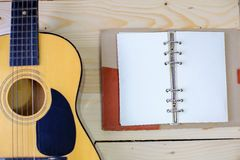 Guitar with a notebook on the wooden floor. Stock Photo