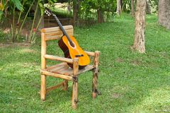Guitar on old rocking chair on grass Stock Photo