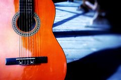 Guitar orange color backgrounds wood shadow outdoors musical instrument arts culture and entertainment blue color nature light. Day no people outdoors light Stock Images