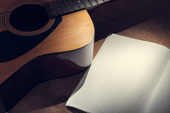 Guitar with paper on wood background Stock Images