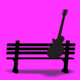 Guitar on a park bench Royalty Free Stock Photo