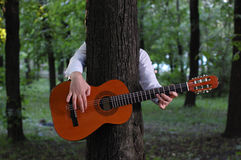 Guitar. park. tree. The man having hidden for a tree plays the guitar Stock Photo
