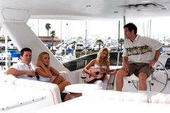 Guitar Party. A casual  group of young adults gathered  on a yacht in the harbor with a blond woman playing guitar Stock Photo