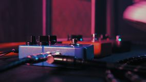 Guitar pedals and footswitch inside recording room. Close up of guitar pedals and musician`s foot tapping on it for stock video footage