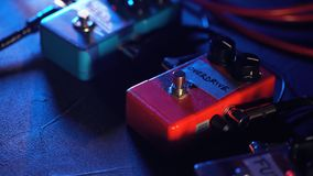 Guitar pedals and footswitch inside recording room. Close up of guitar pedals and musician`s foot tapping on it for stock footage
