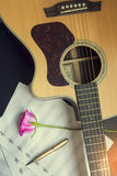Guitar with pen and rose on the note book,vintage filter.  royalty free stock photos