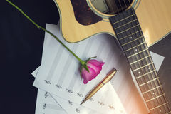 Guitar with pen and rose on the note book,vintage filter Stock Photo