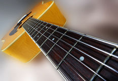 Guitar in perspective. An acoustic guitar photograph taken with a super wide angle lens to exaggerate the perspective Stock Photo