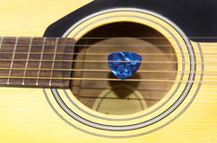 Guitar and pick. Pick tucked in strings of guitar Royalty Free Stock Image