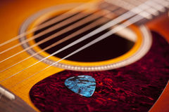 Guitar and pick. Blue guitar pick resting on guitar royalty free stock image