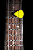 Guitar pick. Yellow guitar pick on the fingerboard close up isolated on black background royalty free stock photo