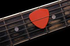 Guitar pick. Orange guitar pick on the fingerboard stock photos