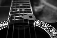 Guitar and pick close up black and white. Close up view of a guitar with decorative details and pick, in black and white stock photography