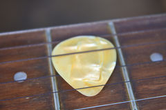 Guitar pick on the fingerboard. Close up Royalty Free Stock Photo