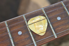 Guitar pick on the fingerboard. Close up Stock Photo