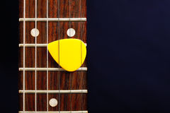 Guitar pick between strings Royalty Free Stock Photos
