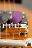 Guitar picks in the guitar strings Royalty Free Stock Photography
