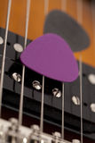 Guitar picks in the guitar strings Stock Images