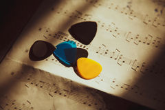 Guitar picks on misic notes. Photo of the guitar picks lying on the music notes Stock Photography
