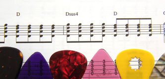 Guitar Picks and Music. Colorful guitar picks are placed on top of sheet music Royalty Free Stock Images