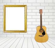 Guitar and picture frame in room Stock Photography