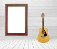 Guitar and picture frame in room Royalty Free Stock Images