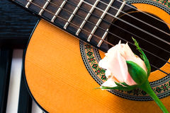 Guitar with pink rose on piano keyboard. Royalty Free Stock Images