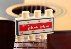 Guitar pitch pipe with acoustic guitar. Guitar pitch pipe on neck of acoustic guitar Royalty Free Stock Images