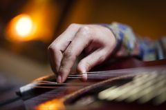 Guitar played by guitarist hand. Detal shot of a guitar player´s hand while plays notes with the strings, musicology ilustrative image with acoustic musical Stock Photos