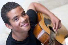 Guitar Player. Young man playing an acoustic guitar, closeup Royalty Free Stock Photos