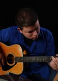 Guitar Player. Man in a blue shirt playing the guitar Royalty Free Stock Photos