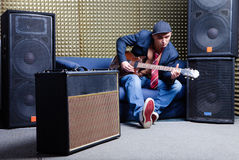 Guitar player. In recording studio at sofa with guitar amplifier and audio systems royalty free stock image
