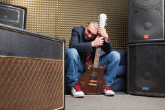 Guitar player. In recording studio at sofa with guitar amplifier and audio systems stock image