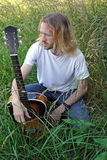 The Guitar Player. An acoustic guitar player poses in a rural field Stock Photos