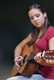 Guitar Player. A beautiful young woman plays the acoustic guitar Stock Images