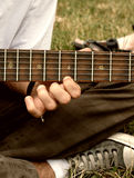 Guitar player. Guitar singer playing guitar on the grass in the park Stock Images