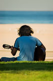 Guitar Player. A young man with long curly hair playing his guitar at the beach stock photography