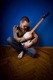 Guitar player. Rocker getting ready to play, adjusting his guitar, looking for the perfect sound. Broad view Royalty Free Stock Images