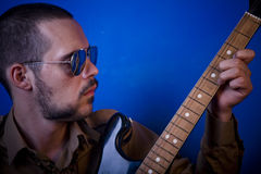 Guitar player. With sunglasses in studio, jamming. Blue background Royalty Free Stock Photos