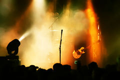 Guitar player in action. On stage standing between fog stock images