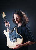Guitar player against the black Stock Photo