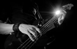 Guitar player with bass guitar. Closeup of guitar player with bass guitar on stage stock image